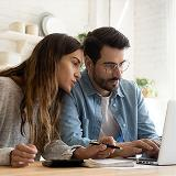man and woman researching homes on laptop