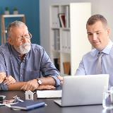 older man speaking with an experienced loan officer