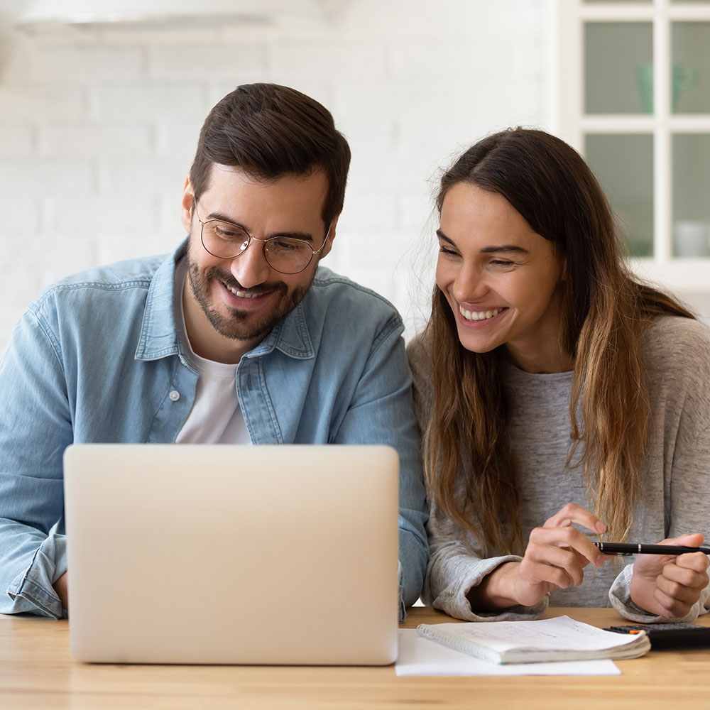 man and woman smiling at laptop after being accepted for an FHA loan